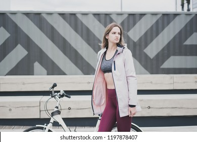 Lifestyle sport concepte. Portrait of sexy young woman with vintage bike in city parking. Nature color toning for design.