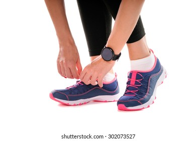 Lifestyle, sport and technology. Close up of female hands with smartwatch tying sneakers. Isolated on white.