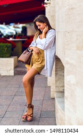 Lifestyle street image of stunning tanned slim pretty brunette woman walking on Paris street, wearing linen beige shorts, caramel leather luxury bag, white shirt and gladiator sandals