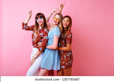 Lifestyle studio portrait of group happy best friends girls dancing and having fun, wearing stylish outfits with tropical prints and vintage dress, enjoy partying, pink background.