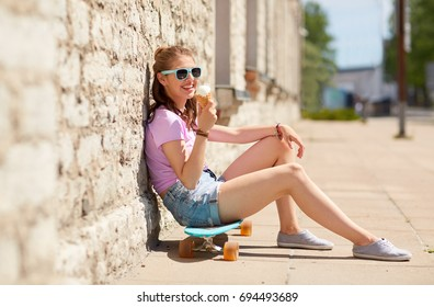 lifestyle, summer and people concept - smiling young woman or teenage girl sitting on longboard on city street and eating ice cream