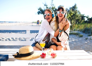 Lifestyle summer portrait of two woman's friends hugs and going crazy together, sitting at beach bar terrace cafe, drinking cocktails and enjoy vacation, bright stylish boho clothes, music headphones.