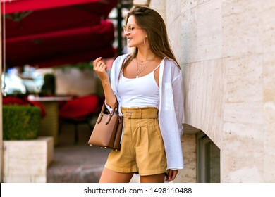 Lifestyle summer portrait of young blissful elegant brunette woman posing on Paris street, wearing casual elegant beige outfit and sunglasses, traveling mood, warm colors.