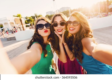 Lifestyle sunny image of best friend girls  taking selfie on  camera, crazy emotions , happy vacations, shopping  day. Wearing elegant dress, way hairstyle, sunglasses and red lips.