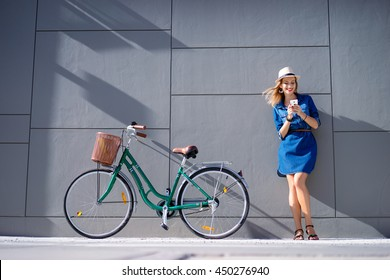 Lifestyle and technology. Young pretty woman using smartphone with bicycle leaning on the grey wall.