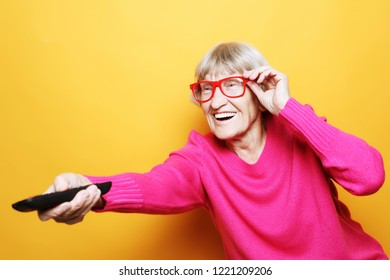 lifestyle, tehnology and people concept: funny grandmother is holding a TV remote over yellow background