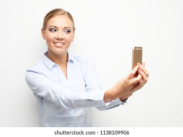 lifestyle, tehnology and people concept: happy young woman is making selfie photo with smartphone.