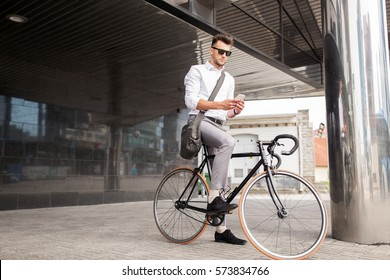 lifestyle, transport, communication and people concept - young man with bicycle and smartphone on city street