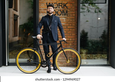 Lifestyle, transport and people concept. young man in sunglasses riding bicycle on city street over brickwall