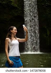 Lifestyle travel blogger. Happy Caucasian woman enjoying waterfall landscape in tropic, taking selfie with smartphone near waterfall. Luxury vacation in Asia. Tibumana waterfall Ubud, Bali, Indonesia