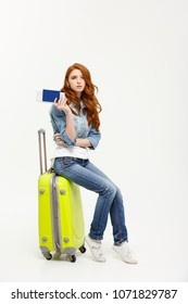 Lifestyle and travel Concept: Young beautiful caucasian woman is sitting on suitecase and waiting for her flight.Isolated over white background.