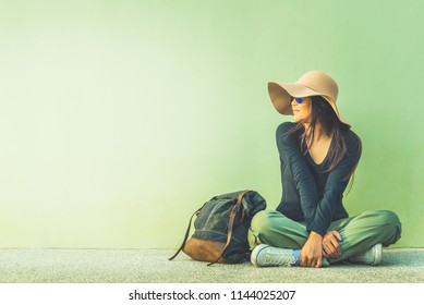 Lifestyle traveler asian girl with backpack sitting on floor near green wall, Tourist woman relaxing joy and looking copy space background, Tourism banner for summer holiday vacation travel concept