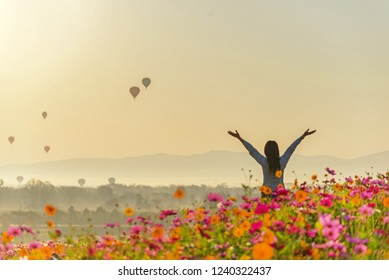 Lifestyle traveler women raise hand feeling good relax and happy freedom and see the fire balloon outdoors the nature tea and cosmos farm in the sunrise morning. Travel and summer Concept