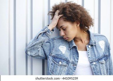 Lifestyle and trendy conceptual photo of African American girl posing in a silver metal wall in a vintage denim jacket . Youth fashion. Portrait head closeup