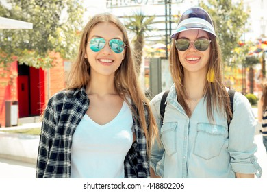 Lifestyle of two best friends in sunglasses laughing outdoor on the street