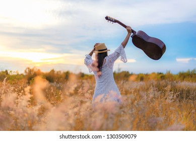 Lifestyle women white dress holding a guitar on a cloudy sunset or sunrise sky in the meadow flower, relax and happy day on summertime,  background field outdoors for inscription.