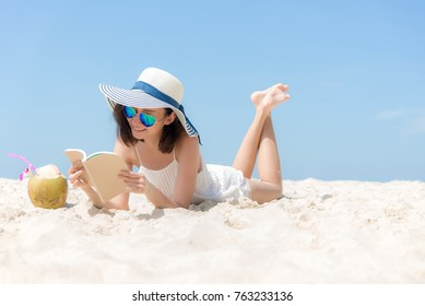 Lifestyle young asian girls woman relax and reading a book at the beautiful coast beach on holiday summer, blue sky background.  Summer Concept.