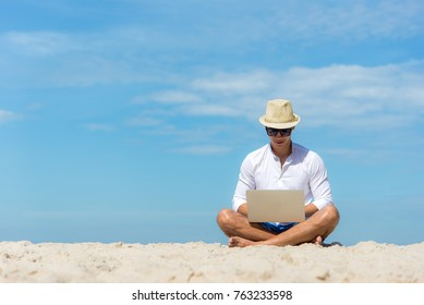 Lifestyle young asian man blogger  working and using keyboard on laptop while sitting on the beautiful beach, freelance travel on holiday summer, blue sky outdoors. Summer Vacation Concept.