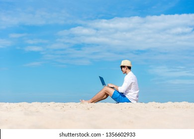 Lifestyle young asian man working on laptop while sitting chill on the beautiful beach, freelance working social on holiday summer.   Summer and Vacation Concept