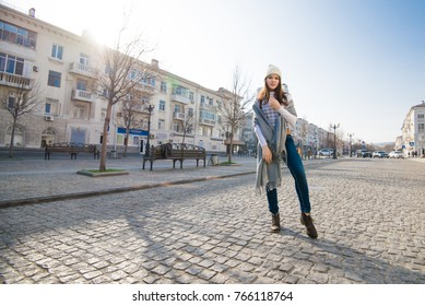 lifestyle young brunette woman with a gray scarf and white hat on the street