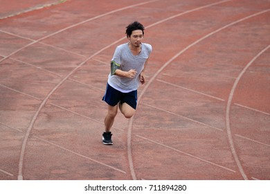 Lifestyle of young healthy Asian runner man running on racetrack in stadium