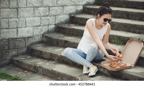 Lifestyle - young woman eating pizza outdoor in street