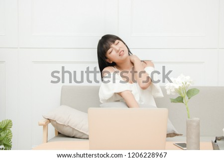 lifestyle - Youngl woman plays computer with bad posture for too long time and suffers from neck pain in home.