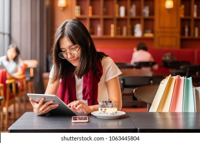 Lifestyle,Technology Concept - Relaxing after day shopping. Beautiful asian woman enjoying tablet computer sitting at a table with cake, mobile phone in a coffee shop.