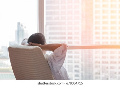 Life-work balance and city lifestyle concept of business man relaxing, take it easy in office room resting with thoughtful mind thinking of living quality looking forward to urban scene