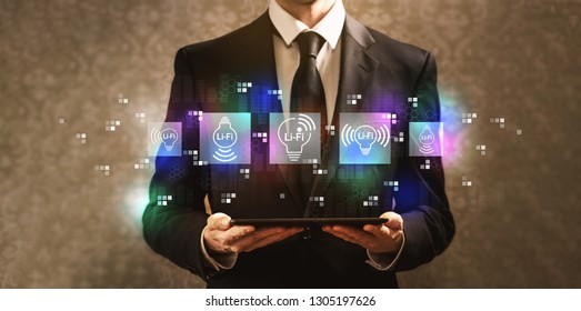 LiFi theme with businessman holding a tablet computer on a dark vintage background
