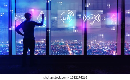 LiFi theme with man writing on large windows high above a sprawling city at night