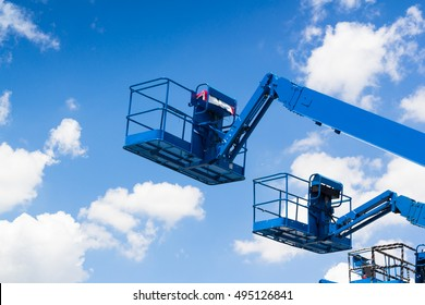 Lift buckets machine against blue sky