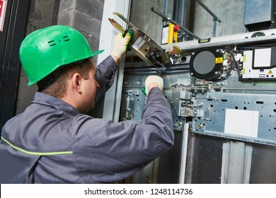 lift machinist adjusting elevator mechanism