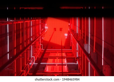 Lift shaft in a residential building. Elevator corridor in the building lit by red elumination. Futuristic elevator shaft is located in a high tower. Abstract, background. Bottom view