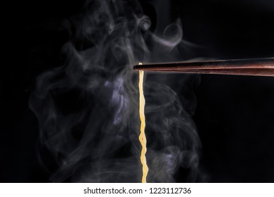 lift with wood chopsticks and fork to pickup noodle with steam and smoke isolated on black background. korea, japan, china, Vietnam and Asian  noodle junk food concept