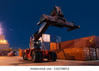 Lifter truck moving freight cargo containers on industrial working site at night