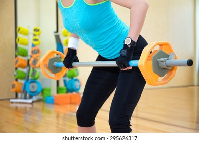 lifting concept - sporty woman exercising with barbell in gym