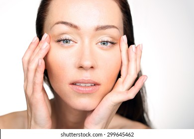 Lifting eye area. Portrait of a woman looking at her face and looking at the first wrinkles at the eyes.