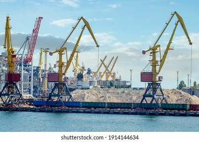 Lifting harbor cranes and railway wagons in the cargo seaport.