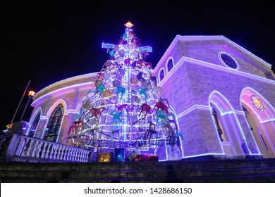 LIGAO, ALBAY / PHILIPPINES - DECEMBER 26, 2018: Scenic night view of a illuminated church with a huge Christmas tree created using recycled materials at the Divine Mercy Shrine