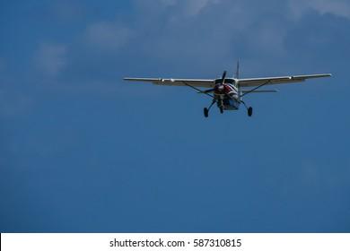 Light aircraft approaching landing over palms
