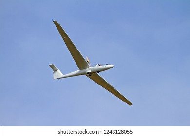 light aircraft or microlight aircraft flying low in the sky above a country house in Montecassiano in Le Marche region of Italy on a clear sunny day