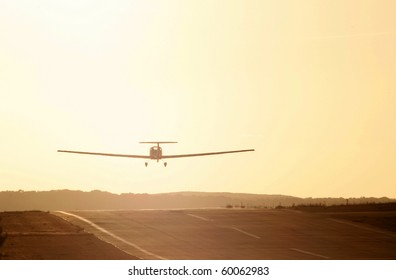 Light aircraft taking off into sunset