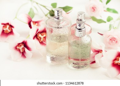 Light aroma perfume bottles wet with water drops surrounded by pink flowers on white bathroom shelf. Pastel colors toned. Feminine delicate scents product.