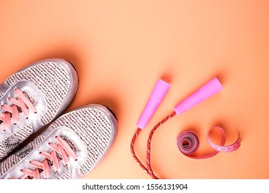 Light athletic sneakers, a skipping rope with pink handles and a pink centimeter on a peach background with a place for your text