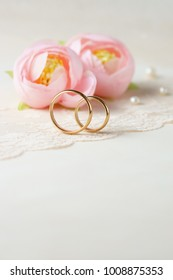 Light background with wedding rings and flowers.