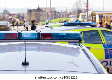 Light bars on unidentified British police vehicles attending an incident in a busy town or city