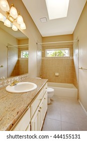 Light bathroom interior with wooden cabinets, large mirror and tile floor.