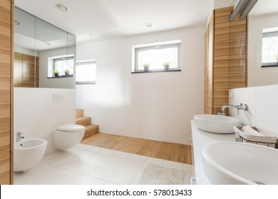 Light bathroom with toilet, two sinks, wide mirrors and wainscot