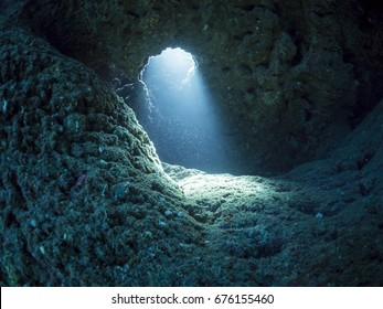 Light beam coming into a collapsed underwater cavern from a window.
